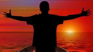 Dankbarkeit für erfülltes Leben: Mensch mit Freudengeste in einem Boot bei Sonnenuntergang